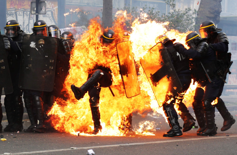 Image:  Image: French CRS anti-riot police officers are engulfed in flames