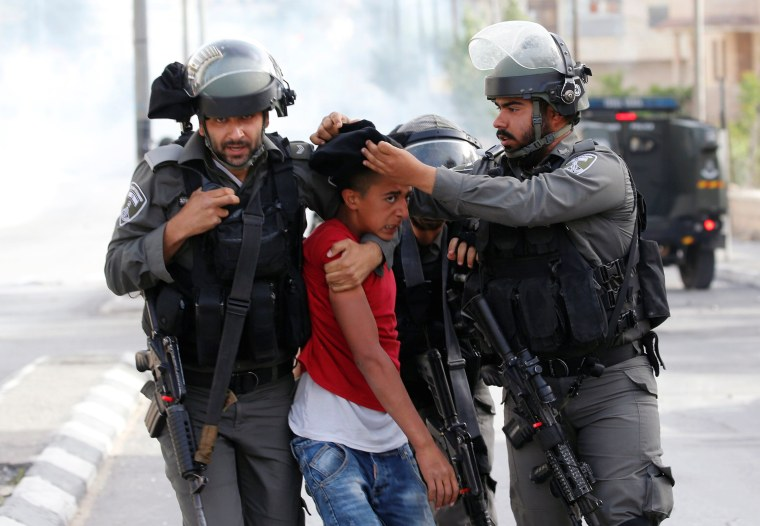 Image: Israeli border police officers detain a Palestinian protester