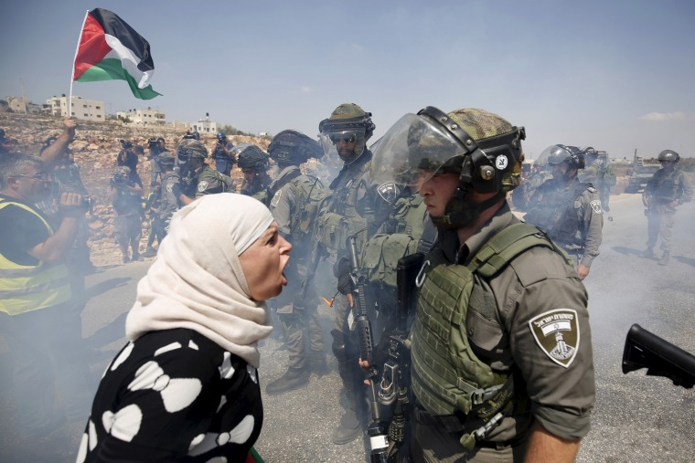 Image: A Palestinian woman argues with an Israeli border policeman during a protest