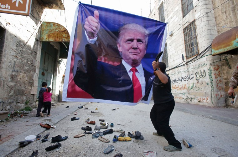 Image: A Palestinian demonstrator throws an old shoe at a poster of US President Donald Trump