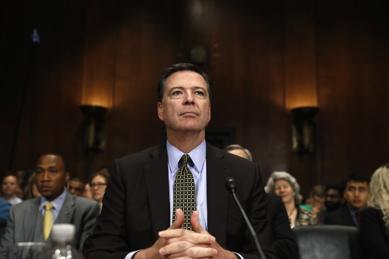 Image: FBI Director James Comey prepares to testify on Capitol Hill