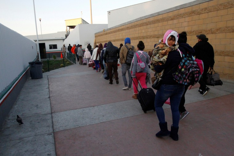 Image: FILE PHOTO: Immigrants from Central America and Mexican citizens, who are fleeing from violence and poverty, queue to cross into the U.S. to apply for asylum at the new border crossing of El Chaparral in Tijuana