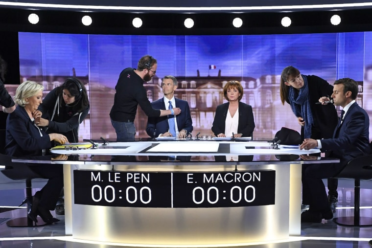 Candidates for the 2017 presidential election, Emmanuel Macron, head of the political movement En Marche !, or Onwards !, and Marine Le Pen, of the French National Front (FN) party, take their places before the start of a debate in La Plaine-Sainte-Denis