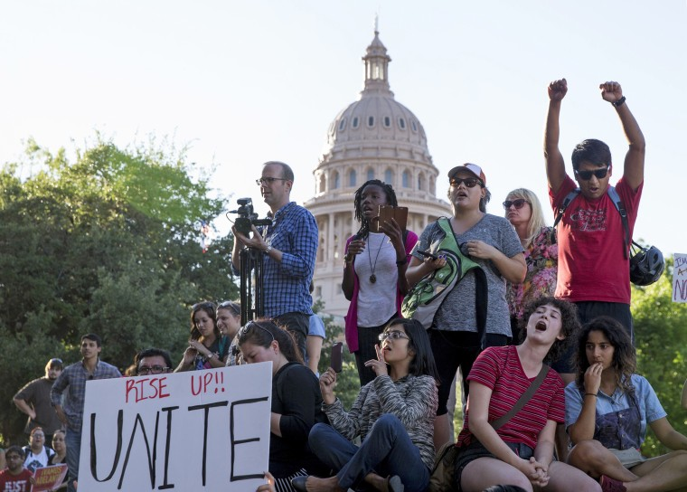 Image: Protesters, who are against the Senate Bill 4 Sanctuary Cities ban, rally outside the Texas Department of Insurance building