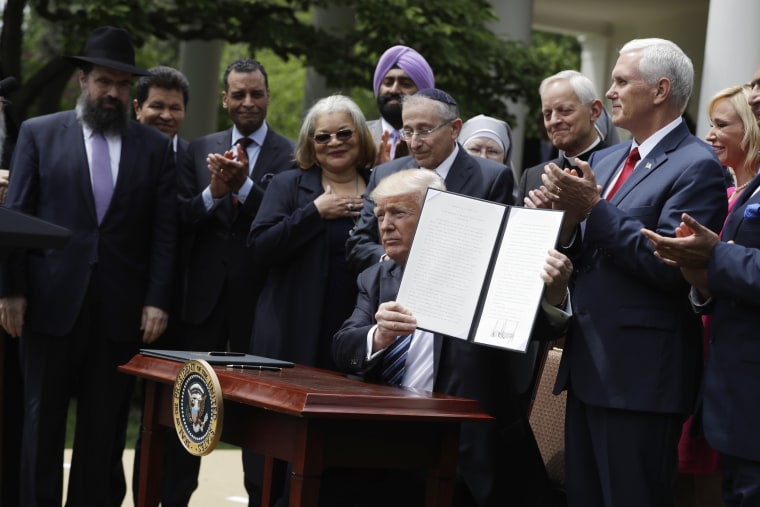 Image: Donald Trump holds a signed executive order