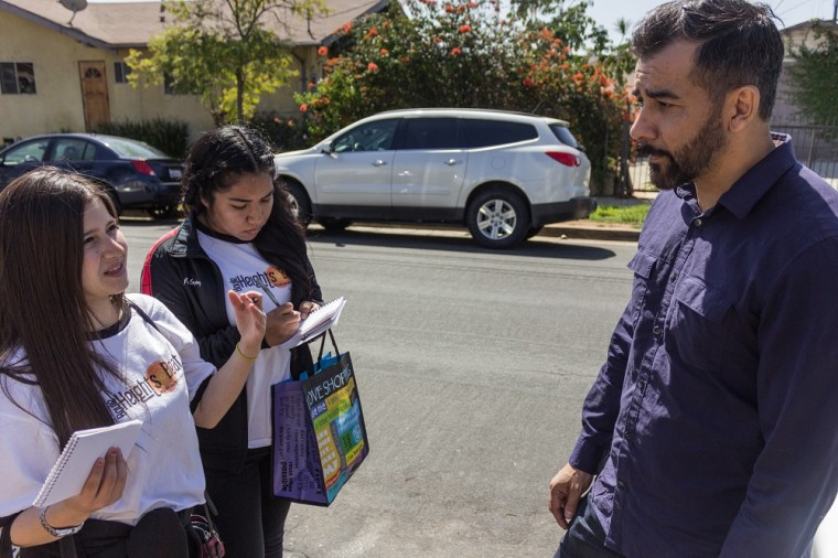 Boyle Heights Beat reporters Samantha Olmos and Jennifer Lopez speak to a participant at a neighborhood walk informing residents of effects of contamination by Exide Technologies.