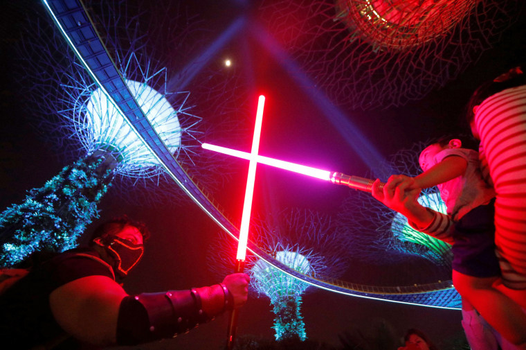 """Image: A fan dressed in a costume """"duels"""" with a fan during activities to mark """"May the 4th"""" Star Wars Day at Gardens by the Bay in Singapore"""