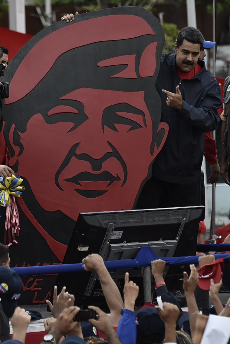 Image: President Nicolas Maduro stands next to a placard depicting late leader Hugo Chavez