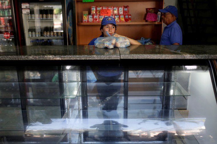 Image: A saleswoman holds bags of bread as she waits for customers at a bakery in Caracas, Venezuela, March 17, 2017.