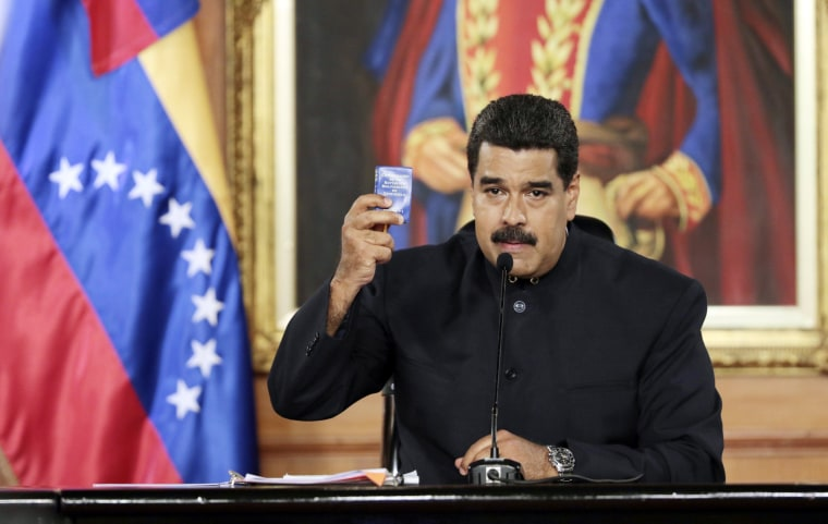 Image: A handout photo made available by the Miraflores Palace's Press Office shows Venezuelan President Nicolas Maduro showing a small copy of the National Constitution in Caracas, Venezuela, May 1, 2017.