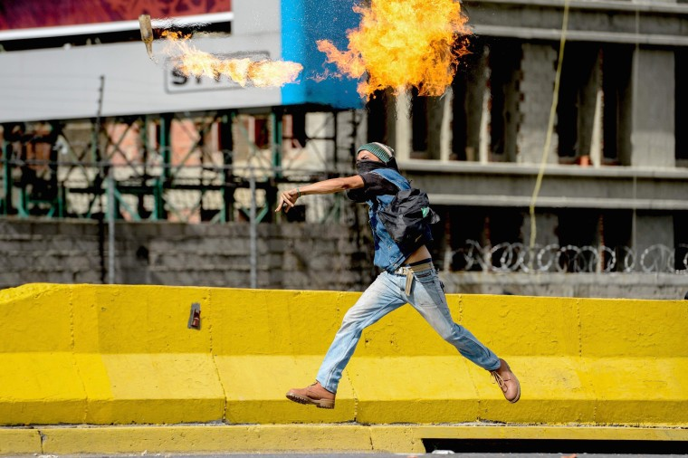 Image: An opposition activist throws a Molotov cocktail at the police during clashes on May Day, in Caracas on May 1, 2017.
