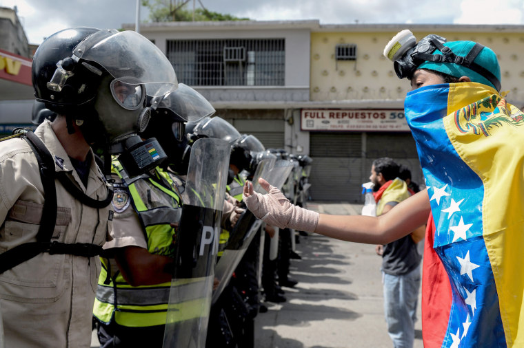 Image: A Venezuelan opposition activist faces police agents during a march against President Maduro, in Caracas on May 1, 2017.