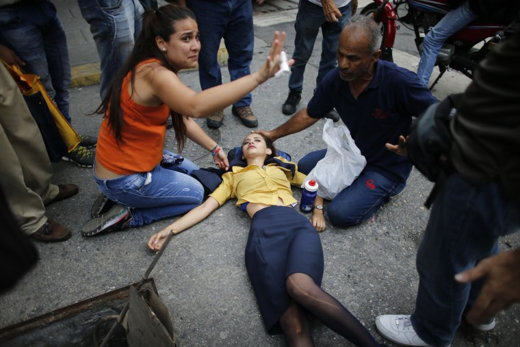 Image: A woman is aided by fellow demonstrators after falling, overcome by tear gas, during anti-government protests in Caracas, Venezuela, April 20, 2017.