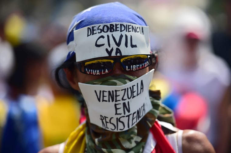 Image: A demonstrator calls for civil disobedience during a protest at the east side of Caracas on April 19, 2017.