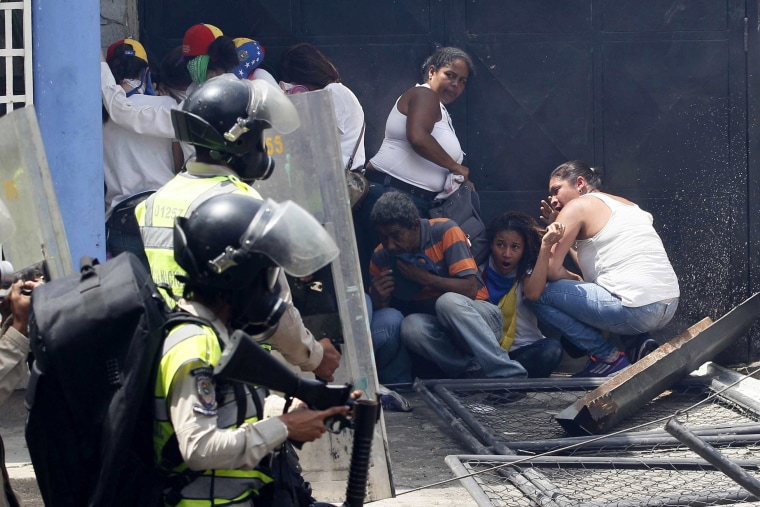 Image: Anti-government demonstrators take cover from advancing Bolivarian Police officers.