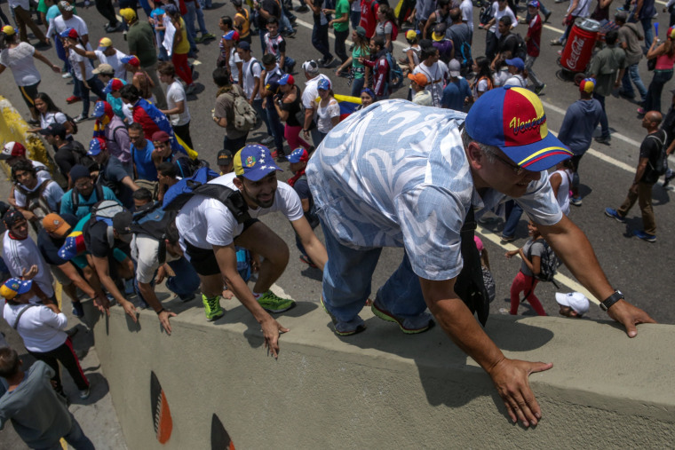 Image: Hundreds of people protest while some climb a bridge in Caracas, Venezuela, on April 10, 2017.