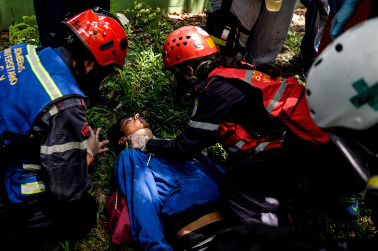 Image: An injured activist is assisted after clashes with riot police at the Central University of Venezuela in Caracas on May 4, 2017.