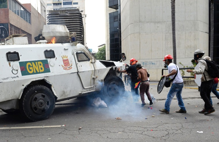 Image: A Venezuelan National Guard riot control vehicle runs over an opposition demonstrator during a protest in Caracas on May 3, 2017.