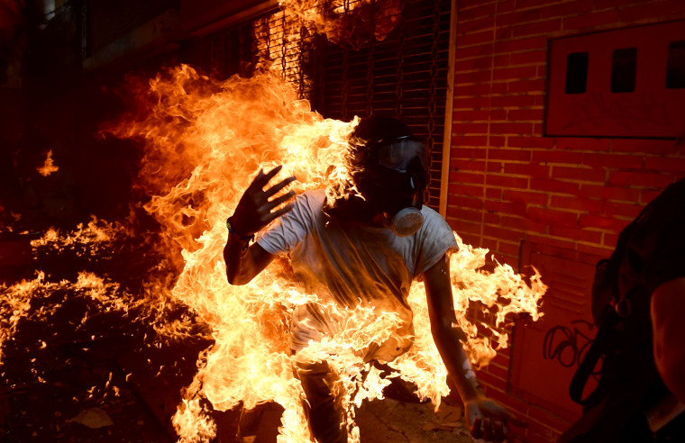 Image: A demonstrator catches fire during clashes with riot police in Caracas on May 3, 2017.