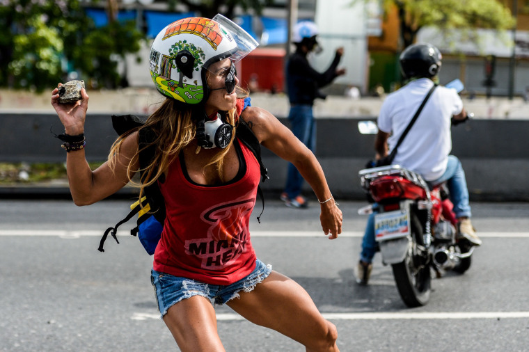 Image: An opposition activist clashes with the police during a march against Venezuelan President Nicolas Maduro