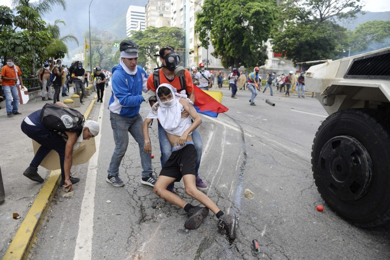 Image: An opposition demonstrator ran over by a National Guard control vehicle is dragged away