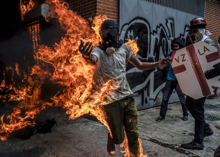 Image: A demonstrator catches fire after the gas tank of a police motorbike exploded