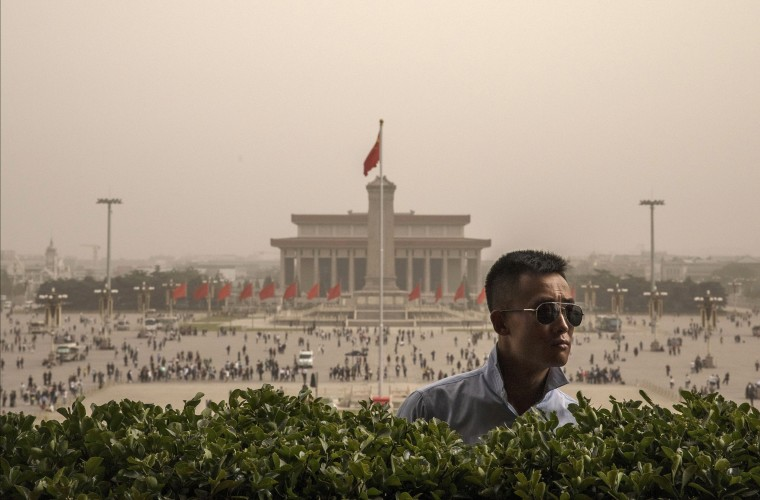 Image: A Chinese police officer stands guard during a sandstorm