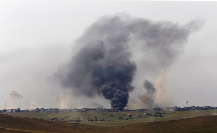 Image: Smoke is seen as members of the Iraqi Army clash with Islamic State fighters at a frontline in north west of Mosul