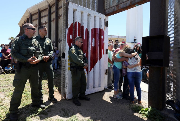 Image: Member of the Reyes family hug as they are reunited for three minutes as U.S. Border patrol agents open a single gate to allow families to hug along the Mexico border as part of Children's Day in Mexico, at Border Field State Park in San Diego