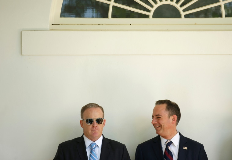 Image: Spicer and Priebus watch as Donald Trump presents the U.S. Air Force Academy football team with the Commander-in-Chief trophy in the Rose Garden of the White House in Washington