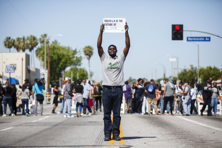 Image: A peace activist participates in a rally on the 25th anniversary of the LA riots