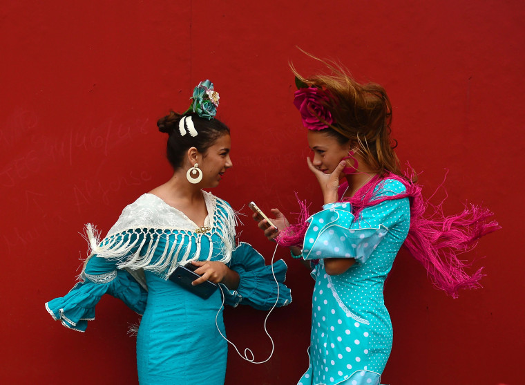 """Image: Two girls wearing traditional Sevillian dresses talk during the """"Feria de Abril"""""""