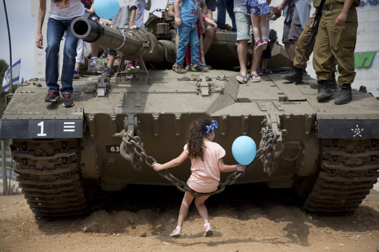Image: Israeli children play on an army tank displayed by the Israeli military