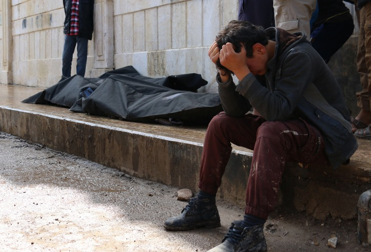 A Syrian man cries next to a body in Azaz, northern Syria.