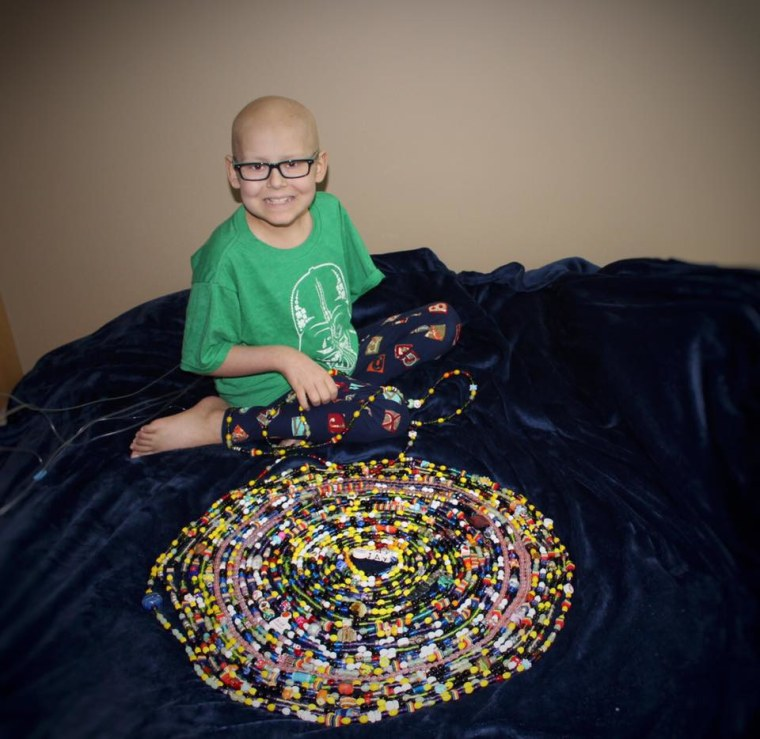 """Jay with his """"beads of courage,"""" a collection of beads symbolizing aspects of his treatment such as chemotherapy sessions, blood transfusions and nights spent in the hospital"""
