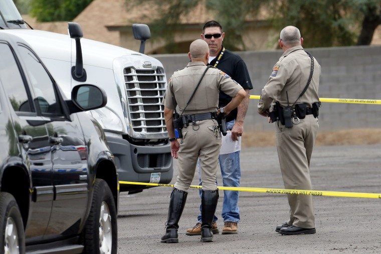Arizona Department of Public Safety officers stand near a tractor trailer shortly after it was shot near 67th Ave and I-10, Thursday, Sept. 10, 2015 in Phoenix. Numerous shootings of vehicles along I-10 over the past two weeks have investigators working around the clock to find a suspect in a spate of recent Phoenix freeway shootings that have rattled nerves and heightened fears of a possible serial shooter.