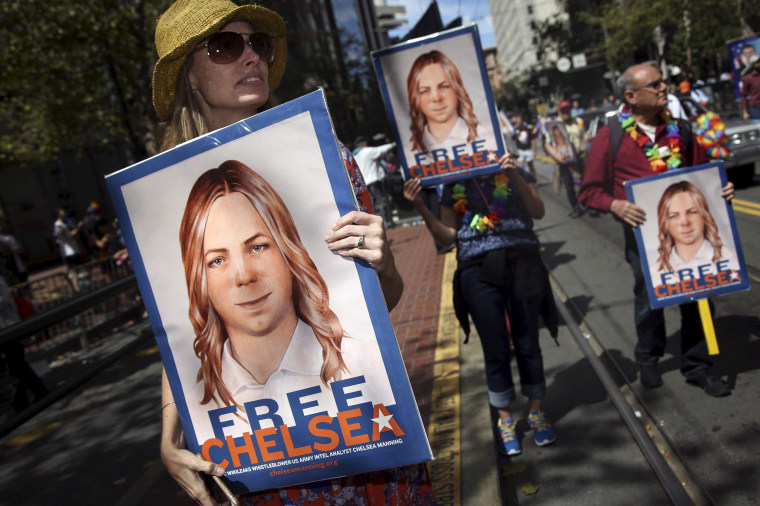 People hold signs calling for the release of imprisoned wikileaks whistleblower Chelsea Manning while marching in a gay pride parade in San Francisco, California June 28, 2015.