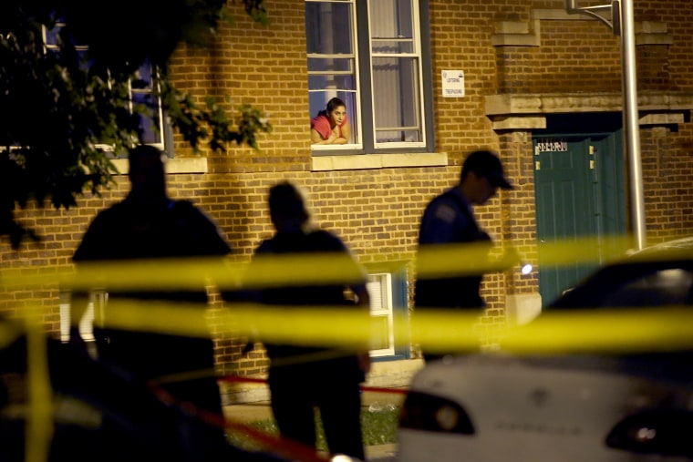 Image: A woman watches from her window as police look for evidence after 20-year-old Carlos Barron was shot and killed in the Humboldt Park neighborhood on July 19, 2013 in Chicago, Illinois.