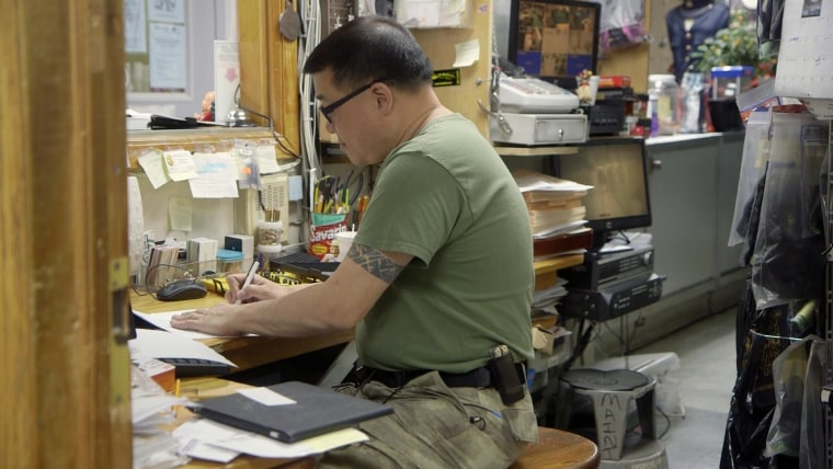 Westside Rifle and Pistol Range owner Darren Leung working in his office.