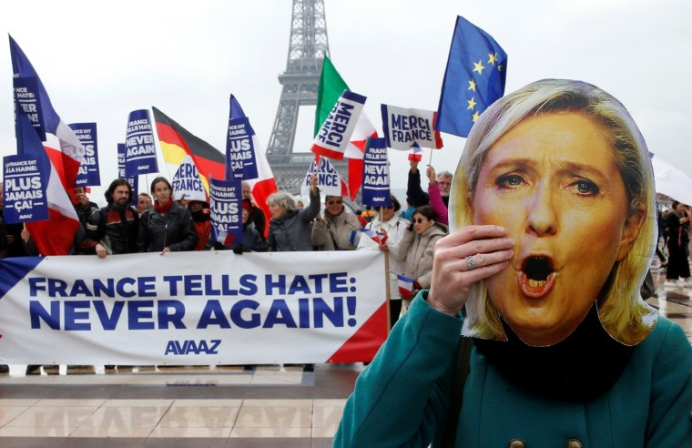 """Image: A protester holds a Marine Le Pen mask near banner reading """"France Tells Hate: Never Again"""""""