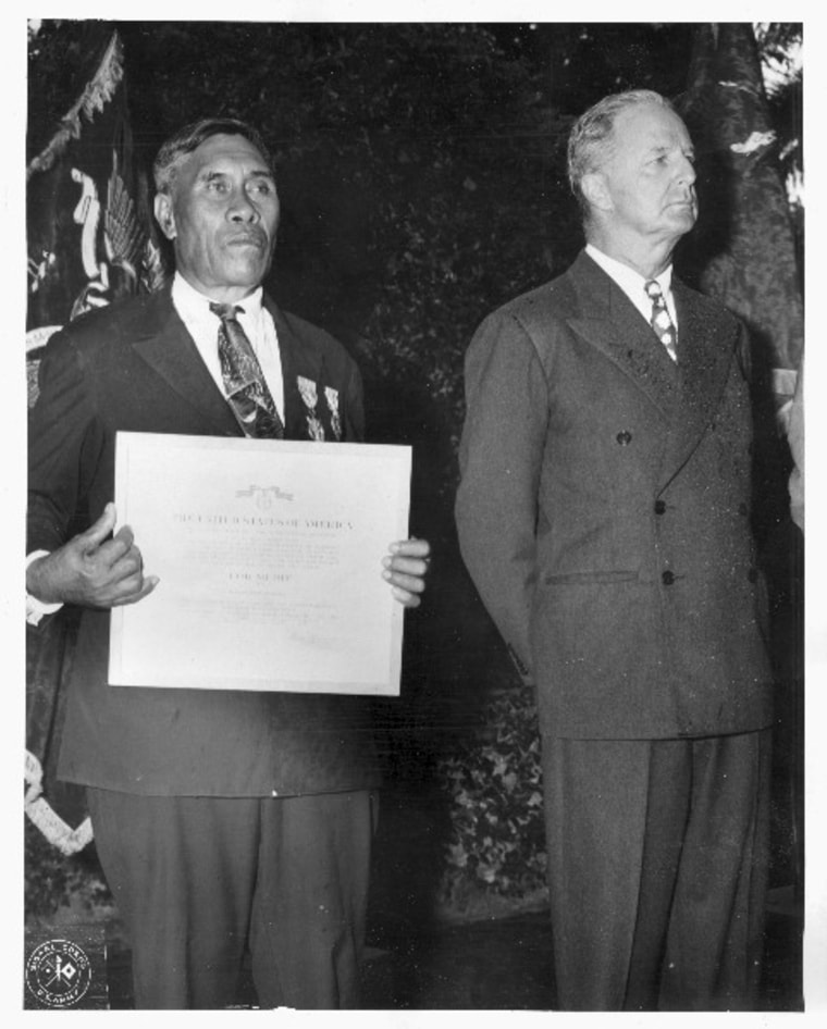 "Benehaka ""Ben"" Kanahele (left), of Niihau, Hawaii, displays the Medal for Merit and Purple Heart awarded to him for killing a Japanese Pilot who landed on Niihau after the Dec. 7, 1941, attack on Pearl Harbor. The pilot shot Mr. Kanahele three times before being killed by the Hawaiian."