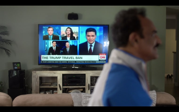 "A scene from ""Unfair and Ugly,"" where the TV is tuned to CNN with the banner, ""Trump Travel Ban."""