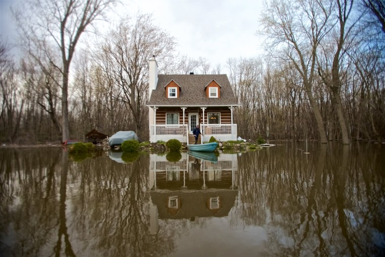 Image: A house is surrounded by floodwaters in Pointe-Calumet, Quebec