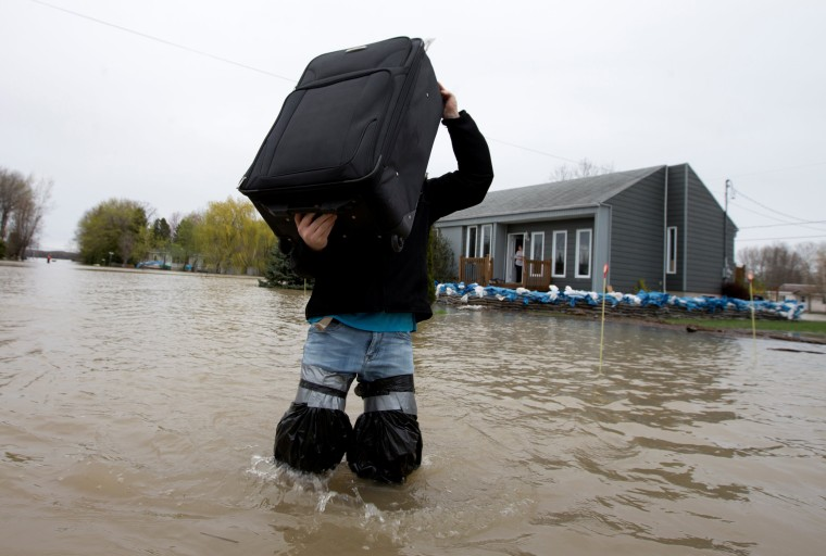Image: A resident removes belongings from his  home in a flooded residential neighbourhood in Rigaud, Quebec