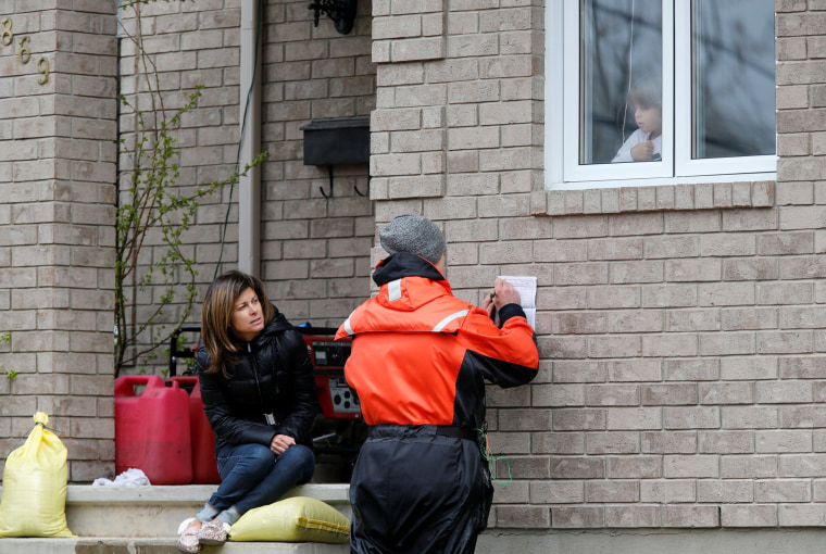 Image: A city official checks on Stephanie Bernier as her son Xavier looks out the window in a flooded residential area in Gatineau