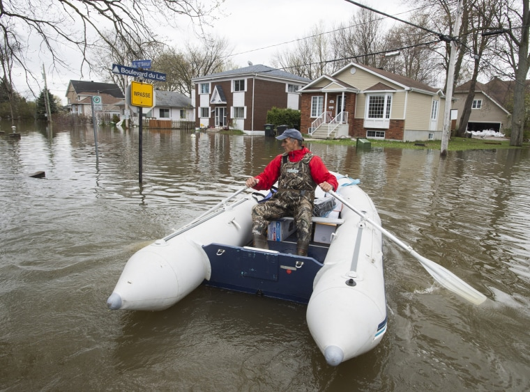 Image: A resident makes his way through flooded streets