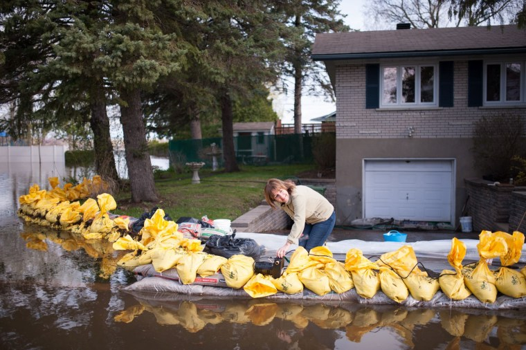 Image: A resident of the Montreal borough of Pierrefonds, uses a pool pump to protect her home from flood waters