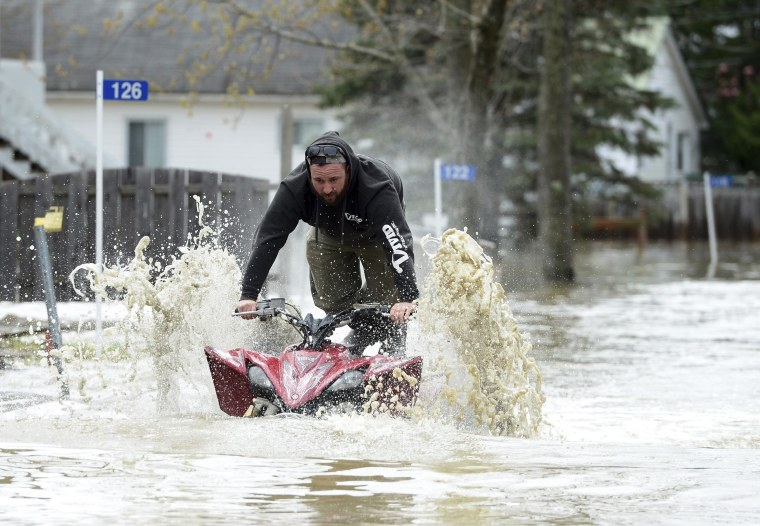 Image: A homeowner drives his ATV down the flooded Chemin Belisle