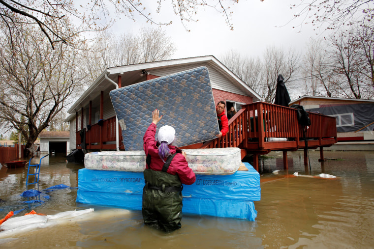 Image: Jean-Francois Perrault and Julie Theriault move mattresses from a home in a flooded residential area in Gatineau