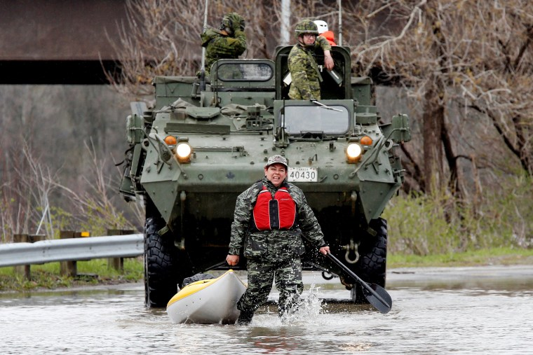 Image: A woman pulls a kayak in front of Canadian soldiers in a flooded residential area in Gatineau